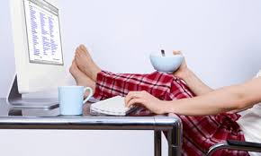 Photo of person in pyjamas with their feet up on the desk to show that freelance life is lazy for some, as explained in Caroline Gibson's blog on how to freelance as a copywriter