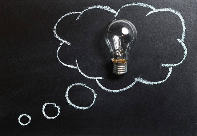Image of a lightbulb on a black background with a thought bubble drawn around it to illustrate thinking up bright ideas, to do with the importance of finding a copywriter who can think, not just write, which is the topic of this blog by strategic copywriter Caroline Gibson