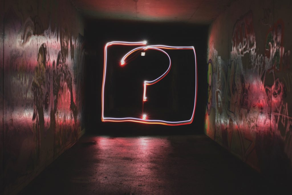 A photo of an illuminated question mark at the end of a tunnel to illustrate the theme of freelance copywriter Caroline Gibson's blog about typical copywriting question she is asked, especially on how much are her copywriting rates or how much she charges for copywriting services.