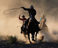 Photo of cowboys on horses with lassoes to illustrate that you sometimes need to chase late paying clients and advice on how to is given in Caroline Gibson's blog on copywriting lessons learned over 25 years