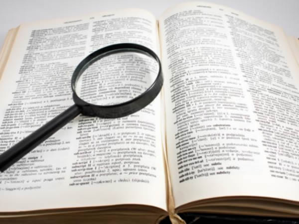 Photo of an open thesaurus and magnifying glass as an example of one place to look for inspiration in how to choose a brand name