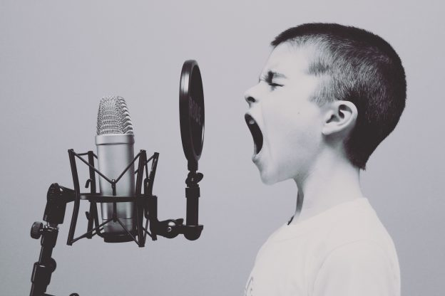 Black and white photo of a boy shouting into a microphone as a visual analogy for voice search and what VEO is, as explained in freelance copywriter Caroline Gibson's blog