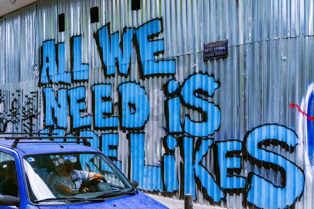Graffiti saying 'All we need is more likes' to illustrate Caroline Gibson's copywriting blog on social media engagement