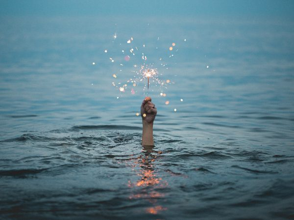 Photo of hand in sea holding sparkler to illustrate blog on how copywriters can start creative during Coronavirus